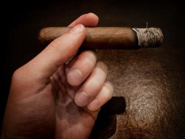 Hand holding cigar with ash against dark background robust smoke.